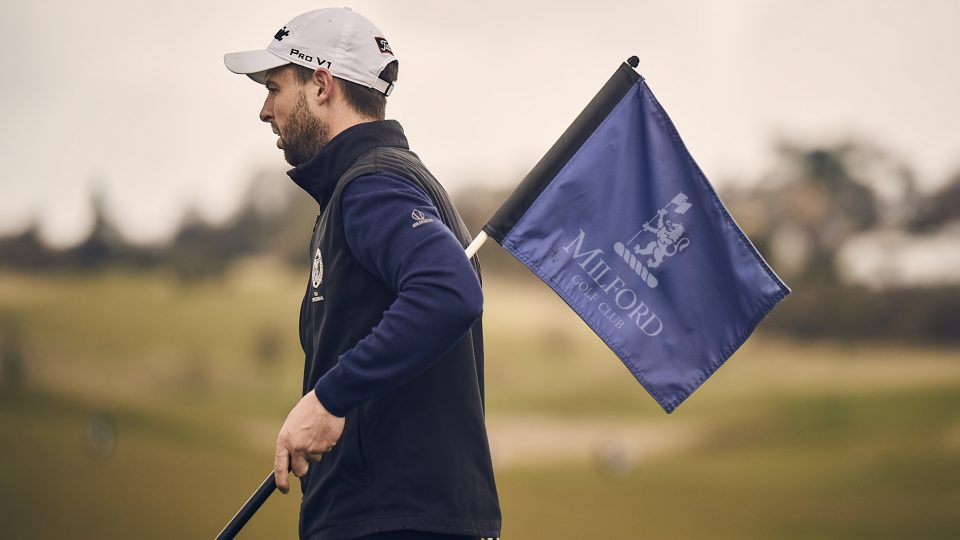 milford golfer holding crown golf flag